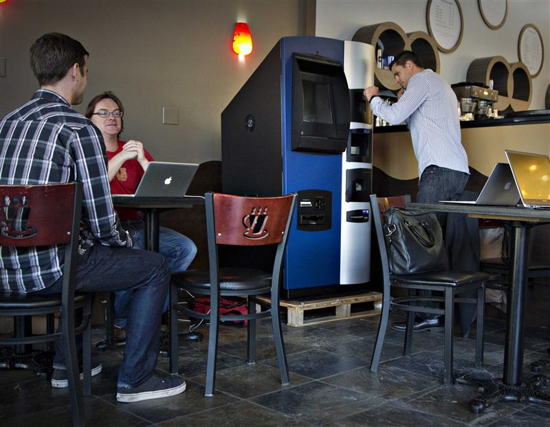 Vancouver Bitcoiniacs Trading Company co-founder Mitchell Demeter prepares, according to him, the first bitcoin ATM machine in a Waves Coffee House in...