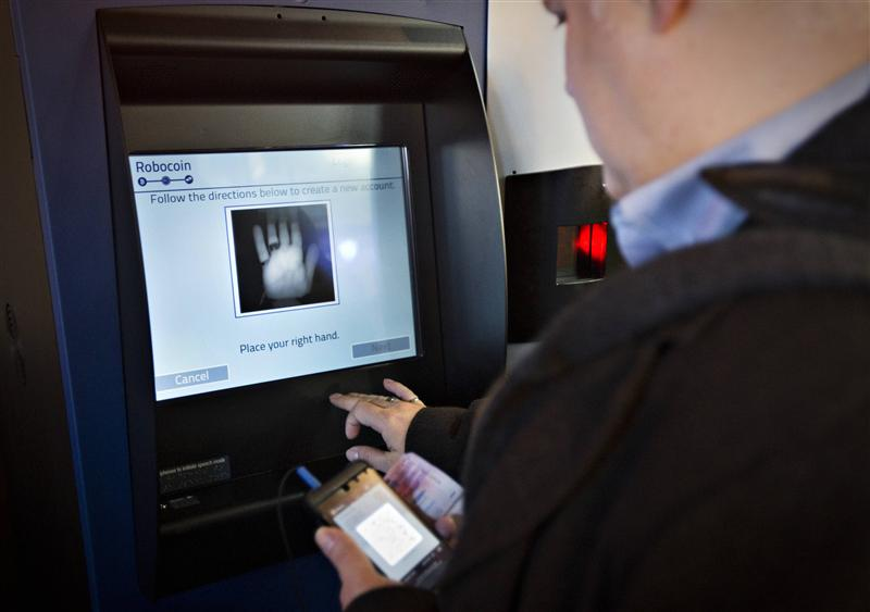 A customer registers his hand print before proceeding on the world's first ever permanent bitcoin ATM unveiled at a coffee shop in Vancouver, British ...