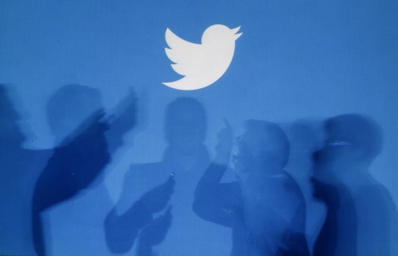 The shadows of people holding mobile phones are cast onto a backdrop projected with the Twitter logo in this illustration picture taken in Warsaw Sept...