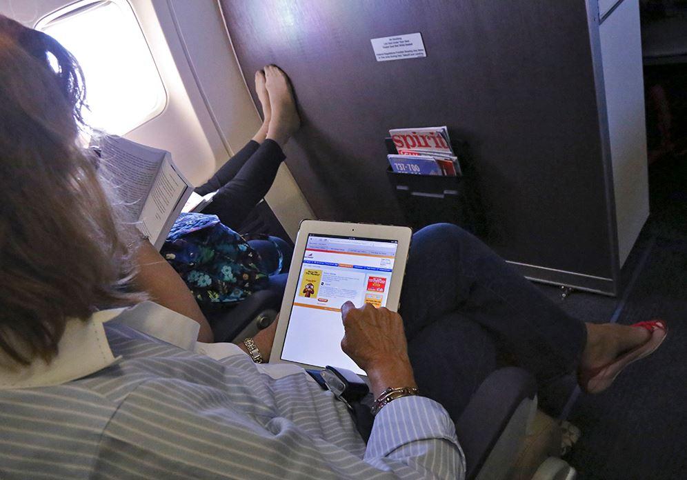 Passenger uses tablet.