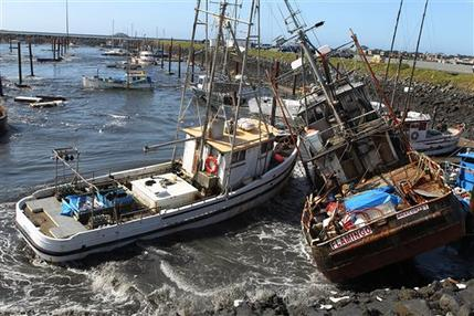 FILE - In this March 11, 2011 file photo, boats collide with one another after a Tsunami surge of water swept through a boat basin in Crescent City, C...