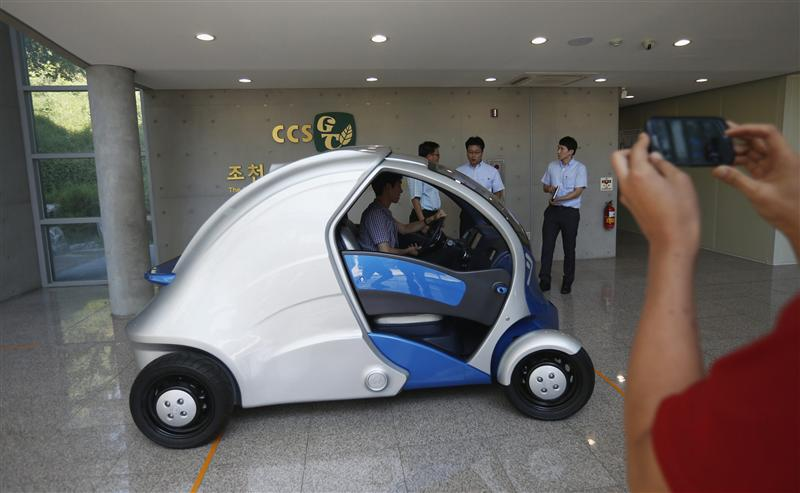 A visitor takes photographs of Armadillo-T, a foldable electric vehicle, at the Korea Advanced Institute of Science and Technology (KAIST) in Daejeon,...