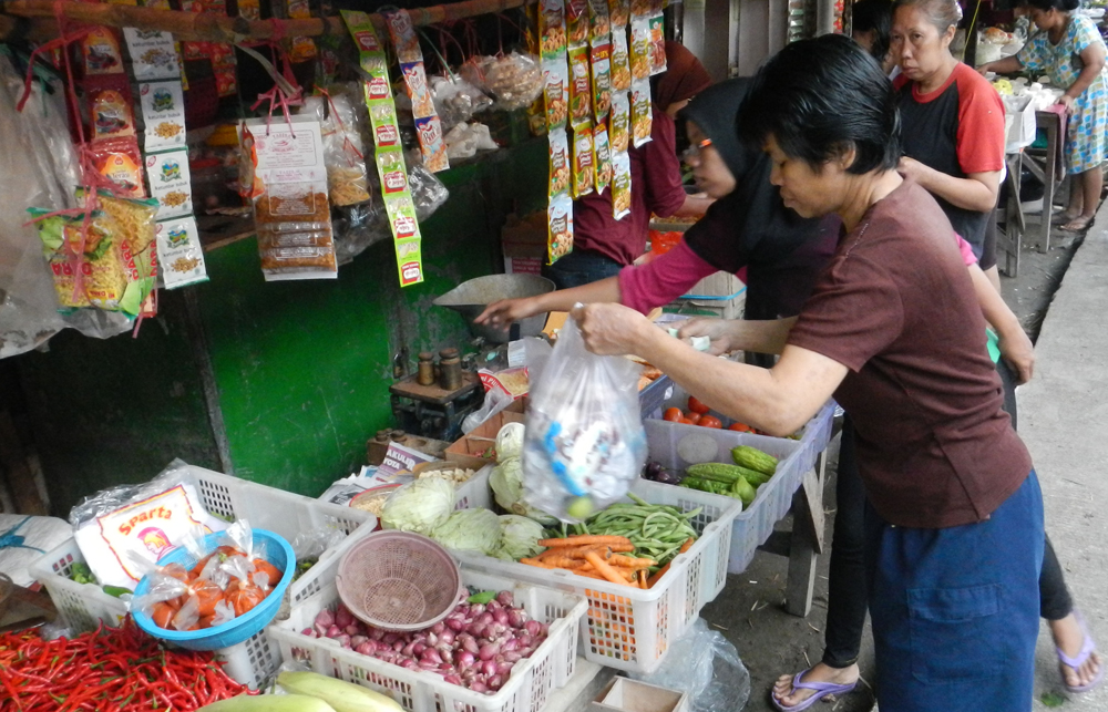 Indonesians buy staple foods as vendors mind their stalls at a traditional street market in Jakarta on Jan. 3.