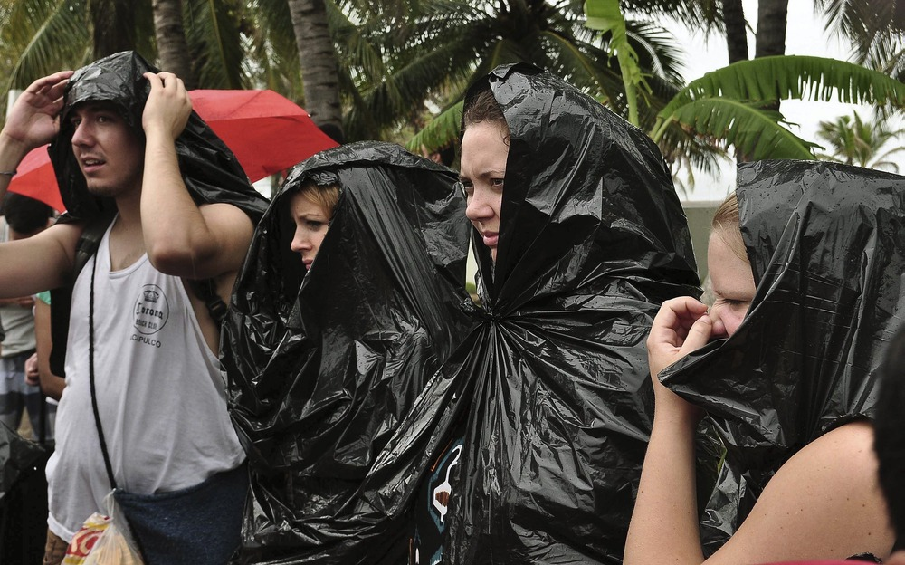 Tourists wrapped in plastic bags wait to be evacuated in a plane of the Mexican Air Force at the Pie de La Cuesta military base in Acapulco, state of ...