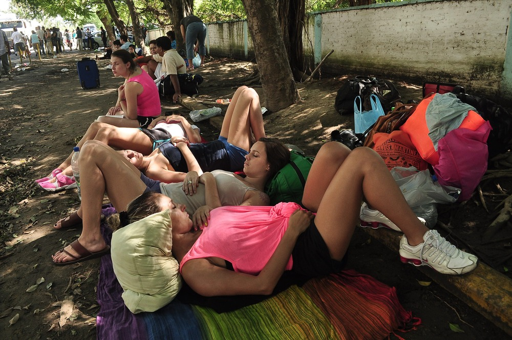 Tourists rest while waiting for a chance to board an outbound Mexican Air Force plane at the Pie de La Cuesta military base in Acapulco, state of Guer...