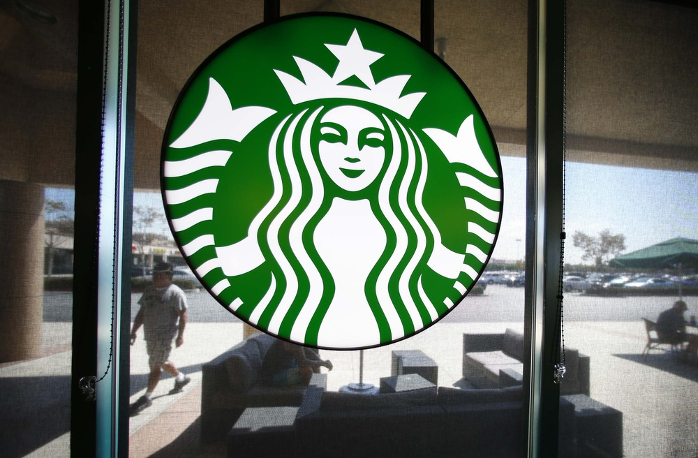 A Starbucks logo hangs on a window at a newly designed Starbucks coffee shop in Fountain Valley, California August 22, 2013.  REUTERS/Mike Blake  (UNI...