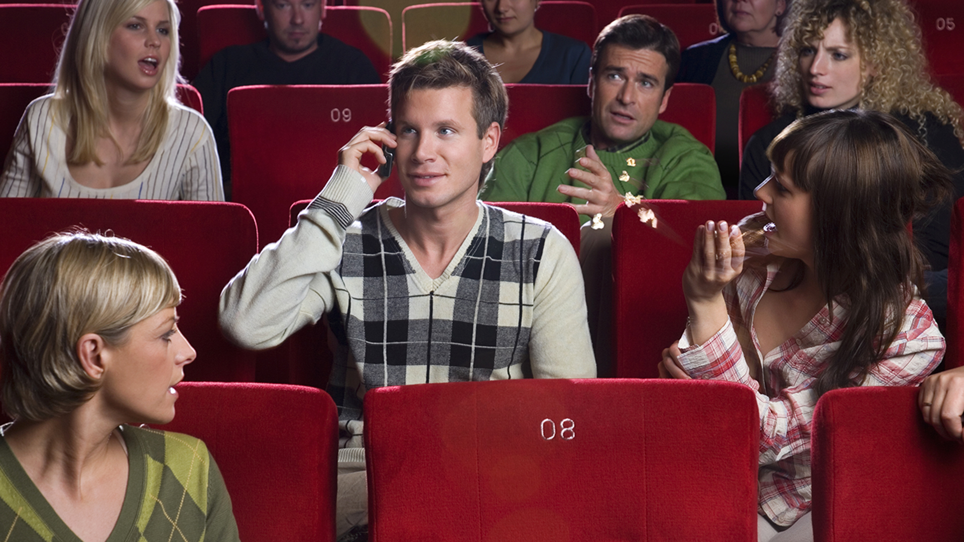 IMAGE: Man talking on cell phone in movie theater