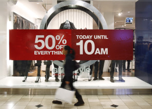 Image: Woman walks by a store's discount advertisement inside the Roosevelt Field Mall in Garden City, New York