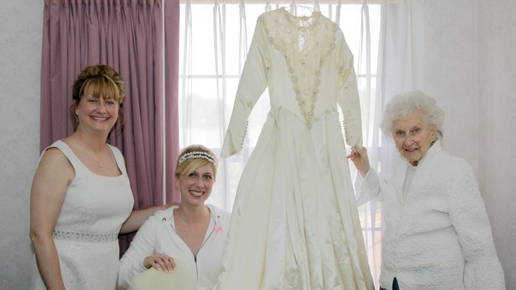 IMAGE: Cindy, Jackie, and Helene pose with their wedding dress.