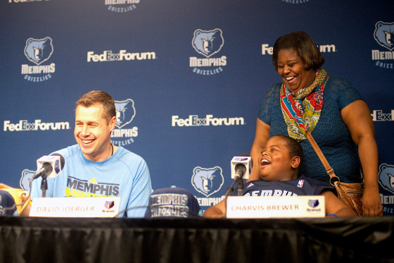 David Joerger, head coach for the Memphis Grizzlies, speaks at a press conference with 8-year-old Charvis Brewer on Sunday. Charvis' mom, Colissa Brewer, laughs happily behind her son.