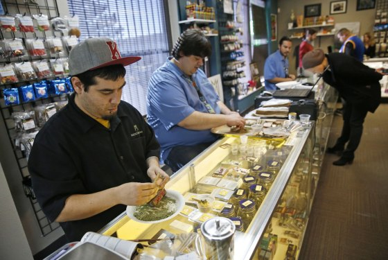 Employees roll joints behind the sales counter at Medicine Man marijuana dispensary, which is among the first batch of Denver businesses to receive their licenses allowing them to legally sell recreational marijuana beginning Jan. 1. 2014.