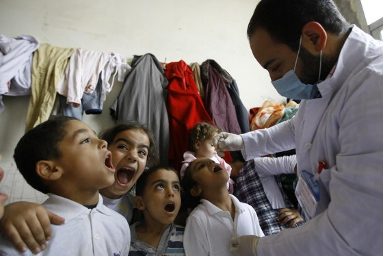 Syrian displaced children line up to receive vaccination against polio at one of the Syrian refugee camps in the southern port city of Sidon, Lebanon,...