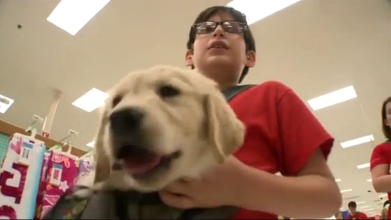 A student named Max holds a puppy in a Target store.
