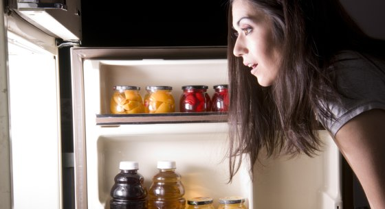 An attractive woman raids the refrigerator late at night looking for a food snack; Shutterstock ID 93209830; PO: MC for TODAY Health