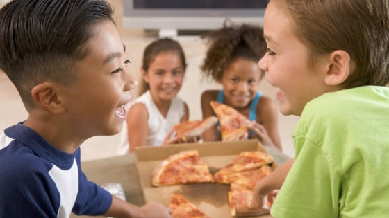 Four young children indoors eating pizza smiling; african; american; boy; caucasian; child; childrens; delivery; eat; enjoying; ethnic; fast; female; ...
