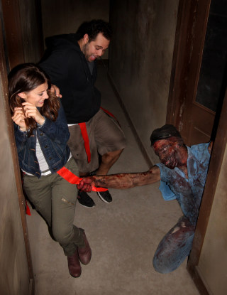 An actor portraying a zombie grabs a flag from the belt of someone walking through the Prison of the Dead Escape, part of the Shocktoberfest attraction in Reading, Pa.