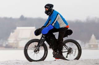 Steve Tannen wears heavy clothing to protect himself against freezing wind chills as he practices for an upcoming bike race in northern Minnesota near...