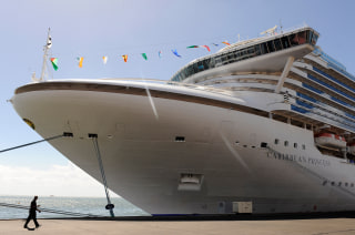 A man passes the Caribbean Princess cruise ship being used as official accommodation for attendees of the CHOGM (Commonwealth Heads of Government Meet...