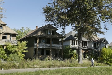 A young man walks in front of a row of abandoned houses in Detroit, Thursday, Sept. 26, 2013.