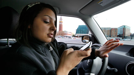 New driver Brandi Eadie, 16, looks down at her cell phone to read a text message as she drives through a rubber-cone course in Seattle on Wednesday, J...