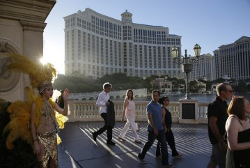 Pedestrians walk by the Bellagio on Aug. 15, 2014, in Las Vegas. This year, hotels will take in a record $2.25 billion in revenue from fees and surcharges, 6 percent more than in 2013 and nearly double that of a decade ago, according to a new study.