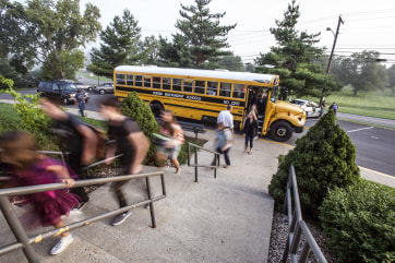 Students get off the bus and head  into school Monday, Aug. 4, 2014, during the first day of school at Burgin Independent School in Burgin, Ky.