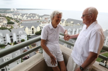Penny and Ty Brown stand on the balcony of their apartment at Westminster-Canterbury in Virginia Beach, Va., on Aug.