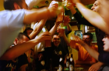 Men toast with glasses of beer in a pub.