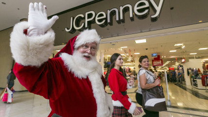 A man dressed as Santa Claus greets shoppers at the Glendale Galleria shopping mall in Glendale, Calif.