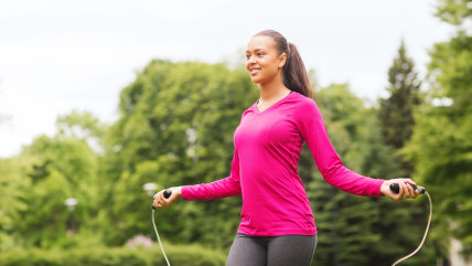fitness, sport, training, park and lifestyle concept - smiling african american woman exercising with jump-rope outdoors; Shutterstock ID 206547886; P...