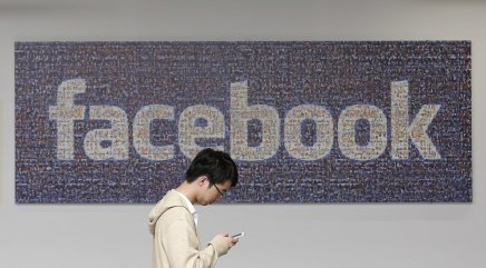 In this June 11, 2014 photo, a man walks past a Facebook sign in an office on the Facebook campus in Menlo Park, Calif. The Proceedings of the Nationa...