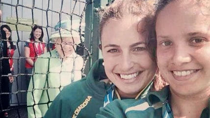 Queen Elizabeth photobombs a pair of Australian national field hockey team members at Thursday's Commonwealth Games in Glasgow, Scotland.