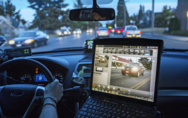 "Tacoma Police Officer Matthew Graham monitors an automatic license plate reader as he cruises during a graveyard shift, June 21, 2014.  In this photo the computer's screen shows the car seen at left with the license plate circled in red. The whole screen would have turned red if the license plate matched one from the ""hot sheet"", indicating a possible stolen car."