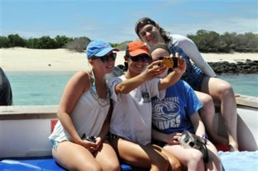 Image: This July 2014 photo provided by Adios Adventure Travel shows a group of American high school students, from left, Isabela Gettier, Elizabeth Thomas, Hannah Whitt Linsly and Stephanie Kirby posing for a group selfie on a trip to the Galapagos.