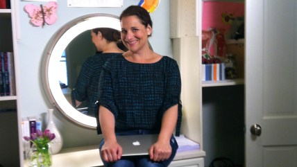 Jennifer Weiner poses at her desk, which sits smack dab in the middle of her closet.