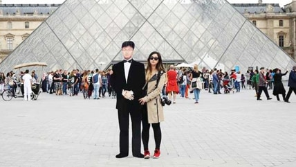 Jinna Yang, 25, is pictured in front of the Louvre while holding a life-size cutout of her late father, Jay Yang. Jinna decided to honor her father and work through her depression over his death by taking a likeness of him to Iceland and through Europe to be photographed in front of famous landmarks.