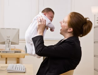 Businesswoman holding baby at desk; Shutterstock ID 48701269; PO: today-moms-sg-welcome; Job: 141103; Client: today.com