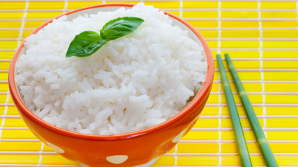 Bowl of steamed rice on yellow with bamboo chopsticks