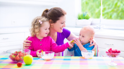 Happy young family, mother with two children, adorable toddler girl and funny baby boy having healthy breakfast eating fruit and dairy, sitting in a w...