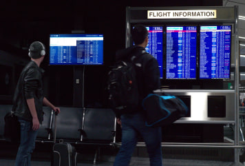 Image: Travelers check the status of flights at Boston's Logan International Airport
