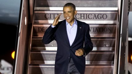 President Barack Obama salutes as he walks off of Air Force One after arriving at O'Hare International Airport in Chicago on Sunday, Oct. 19, 2014. (A...