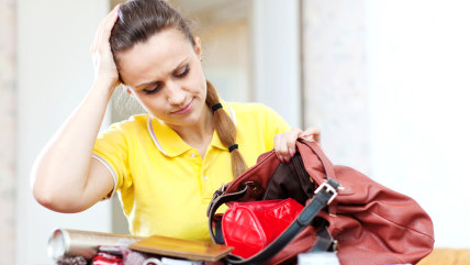 Upset woman lost something  in her purse