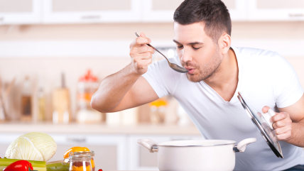 Tasting soup. Handsome young man tasting soup from the pan while standing in the kitchen; Shutterstock ID 187180535; PO: TODAY.com