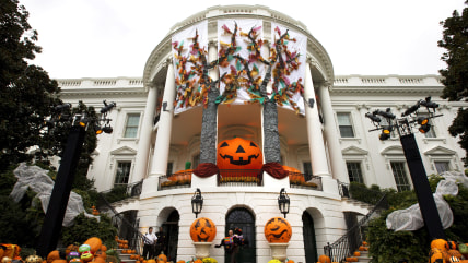 A White House usher takes a model of one of the Obama dogs outside as Halloween decorations adorn the South Portico of the White House in Washington, ...