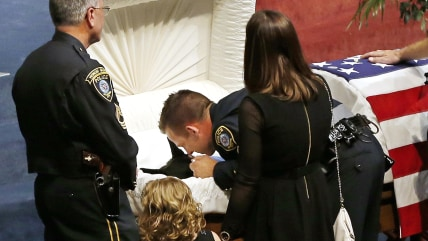 Oklahoma City police officer Sgt. Ryan Stark, center, leans over the casket of his canine partner, K-9 Kye, following funeral services for the dog in ...