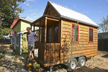 Jay Schafer, owner of Tumbleweed Tiny Houses, exits a tiny house he built for himself in Graton, Calif., in this Oct. 14, 2010, photo.
