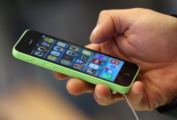 Should you rent or buy the new iPhone 6? It depends on your upgrade habits, experts say. Here, a customer tries out the Apple iPhone 5C smartphone at the Berlin Apple Store on the first day of sales on Sept. 20, 2013.