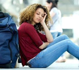 Image: Tired young woman sleeping at airport with luggage