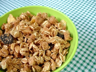 A close up view of a bowl full of granola on a chequered green towel.