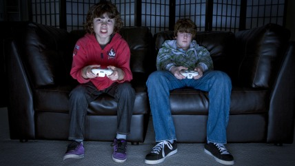 Two boys sitting on a couch playing video games; Shutterstock ID 49428283; PO: TODAY.com